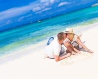 Giovani coppie che si rilassano sulla spiaggia tropicale della sabbia su cielo blu Fotografie Stock Libere da Diritti