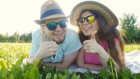 Giovani coppie che si riposano nell'erba e nel sorridere archivi video