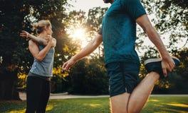 Giovani coppie che si scaldano per l'allenamento di mattina nel parco Immagini Stock