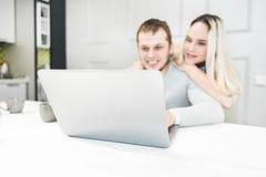 Giovani coppie che si siedono alla mattina in loro cucina e che per mezzo del computer portatile Concetto online di acquisto Cuci fotografia stock libera da diritti
