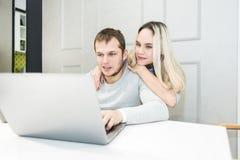 Giovani coppie che si siedono alla mattina in loro cucina e che per mezzo del computer portatile Concetto online di acquisto Cuci immagini stock libere da diritti