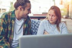 Giovani coppie che si siedono in caffè della via con il computer portatile e che discutono un problema della famiglia Fotografia Stock