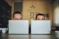 Giovani coppie che si siedono davanti ai computer immagine stock libera da diritti