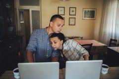 Giovani coppie che si siedono davanti ai computer fotografia stock