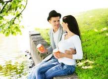 Giovani coppie che si siedono insieme sulla riva del fiume con caffè Fotografia Stock Libera da Diritti