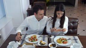 Giovani coppie che si siedono nel ristorante e che prendono le immagini dell'alimento con il telefono cellulare fotografia stock libera da diritti
