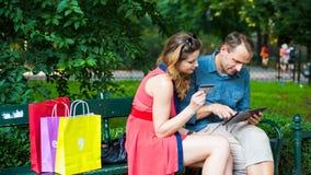 Giovani coppie che si siedono su un banco con i sacchetti della spesa variopinti e la compressa. Fotografia Stock Libera da Diritti