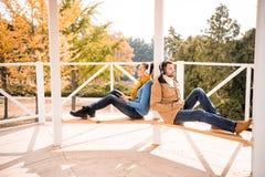 Giovani coppie che si siedono sul banco in cuffie fotografia stock libera da diritti