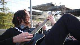 Giovani coppie che si siedono sul banco - un uomo che gioca chitarra e cantare archivi video