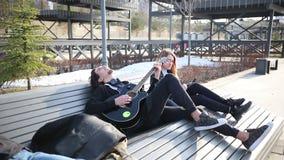 Giovani coppie che si siedono sul banco - un uomo che gioca chitarra archivi video