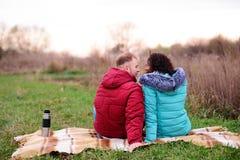 Giovani coppie che si siedono sul plaid e sul caffè della bevanda da un termo immagine stock libera da diritti