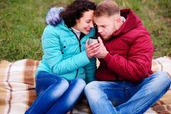 Giovani coppie che si siedono sul plaid e sul caffè della bevanda da un termo fotografia stock libera da diritti