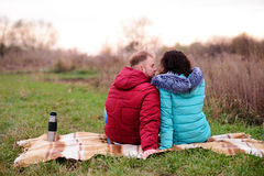 Giovani coppie che si siedono sul plaid e sul caffè della bevanda da un termo immagine stock