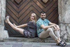 Giovani coppie che si siedono sulla soglia di pietra di vecchia casa Fotografia Stock