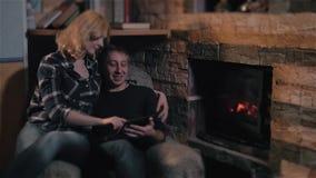 Giovani coppie che si siedono sulla stagione di Sofa Near Fireplace At Winter a casa, uomo che per mezzo del PC della compressa video d archivio