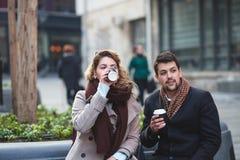 Giovani coppie che si siedono sulla via della città immagini stock libere da diritti