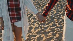 Giovani coppie che si tengono per mano al tramonto sulla spiaggia archivi video