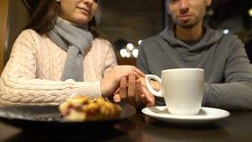 Giovani coppie che si tengono per mano durante la data romantica in caffè, godente insieme del tempo archivi video