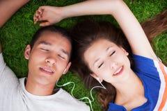 Giovani coppie che si trovano giù sull'erba Fotografie Stock