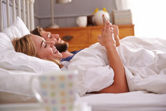Giovani coppie che si trovano a letto facendo uso dei telefoni cellulari Fotografia Stock