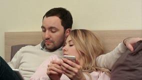 Giovani coppie che si trovano a letto, uomo che per mezzo della compressa digitale, donna annoiata che per mezzo dello smartphone stock footage