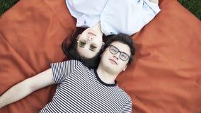 Giovani coppie che si trovano su una coperta sull'erba video d archivio