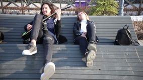 Giovani coppie che si trovano sul banco - un uomo che gioca chitarra video d archivio