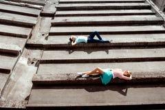 Giovani coppie che si trovano sul tetto grigio della costruzione di appartamento nella ricerca fotografia stock libera da diritti