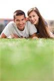 Giovani coppie che si trovano sull'erba Immagine Stock