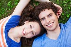 Giovani coppie che si trovano sull'erba Fotografia Stock Libera da Diritti