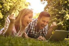 Giovani coppie che si trovano sull'erba fotografia stock