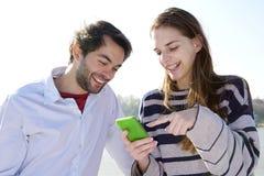 Giovani coppie che sorridono e che esaminano telefono cellulare Fotografie Stock Libere da Diritti