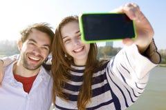 Giovani coppie che sorridono e che prendono selfie con il telefono cellulare Fotografia Stock