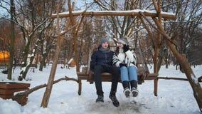 Giovani coppie che sorridono l'un l'altro e che parlano sull'oscillazione nel parco di inverno video d archivio