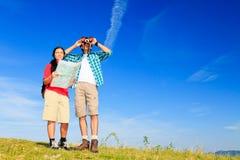 Giovani coppie che stanno alla cima di una collina immagini stock