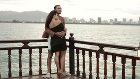 Giovani coppie che stanno alla piattaforma di spostamento della barca d'annata, di conversazione e di abbracciare