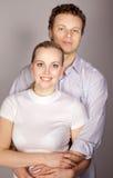 Giovani coppie che stanno insieme, posando nello studio, esaminante Ca Immagini Stock Libere da Diritti