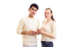 Giovani coppie che tengono le tazze bianche Fotografie Stock