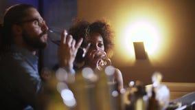 Giovani coppie che tostano il vetro di vino nella barra di lusso datare Pantaloni a vita bassa e donna di colore sulla cena roman video d archivio