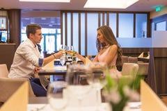 Giovani coppie che tostano nel ristorante con i vetri di vino immagini stock