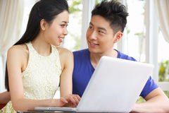 Giovani coppie cinesi allo scrittorio ed al computer portatile usando Immagini Stock Libere da Diritti
