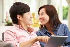 Giovani coppie cinesi per mezzo del ridurre in pani di Digitahi Immagini Stock Libere da Diritti