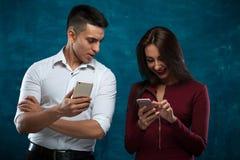 Giovani coppie con gli smartphones su fondo blu Immagine Stock