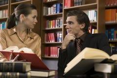 Giovani coppie con i libri allo scrittorio delle biblioteche Immagine Stock