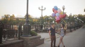 Giovani coppie con i palloni che camminano sulla passeggiata archivi video