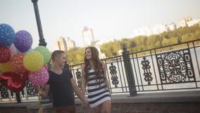 Giovani coppie con i palloni che camminano sulla passeggiata video d archivio