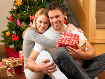 Giovani coppie con i regali davanti all'albero di Natale Immagini Stock Libere da Diritti
