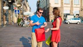 Giovani coppie con i sacchetti della spesa variopinti. Discussione. Immagine Stock Libera da Diritti