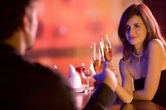 Giovani coppie con i vetri del champagne in ristorante Fotografie Stock