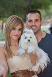 Giovani coppie con il cane maltese dell'animale domestico immagine stock libera da diritti